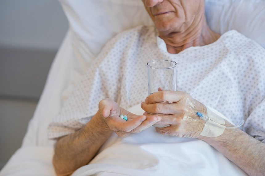elderly man in hospital gown taking pills