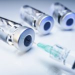 Syringe and glass vials of medicine