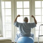 older man sitting on exercise ball at home