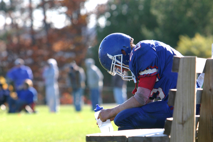 exhausted football player resting on bench
