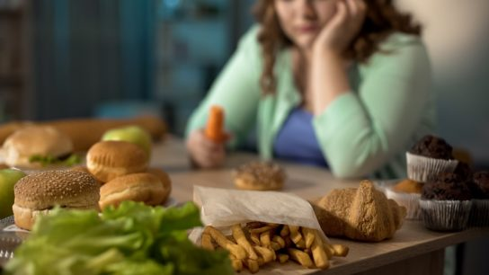 unhealthy junk food on table in front of woman