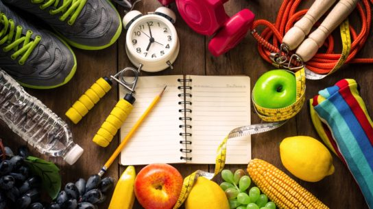 Fitness concept with workout equipment, journal, and healthy foods on wooden background